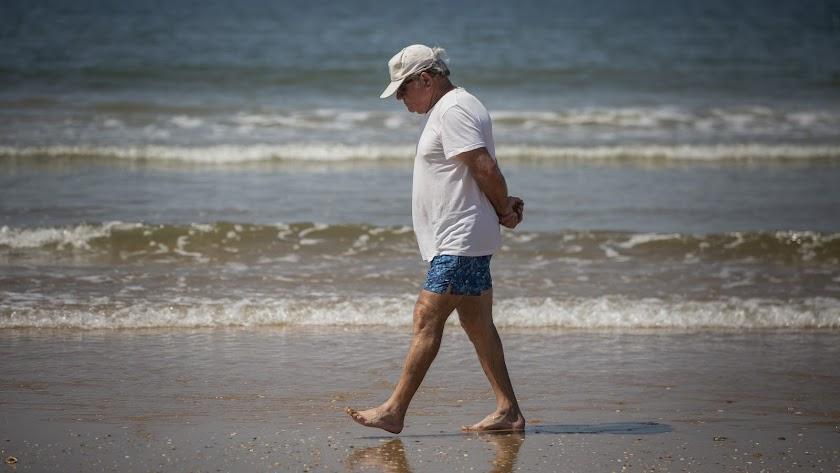 Un hombre pasea por la playa de Punta Umbría.
