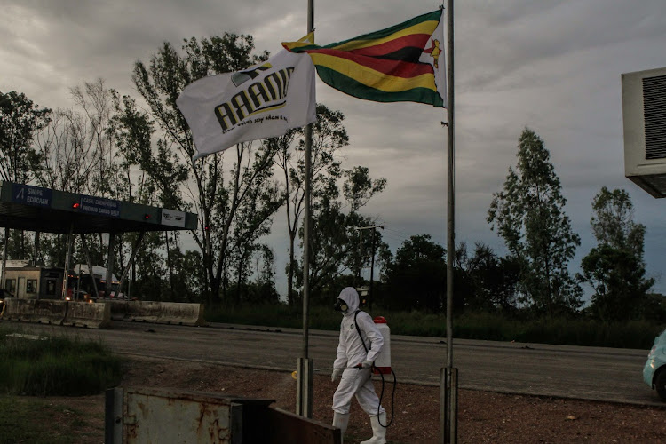 A man disinfects the outside of the toll office using a spraying machine at a toll gate whilst the Zimbabwean flag flies half mast recently in Chinhoyi, Zimbabwe. The country has seen a surge in covid-19 cases and deaths since December.
