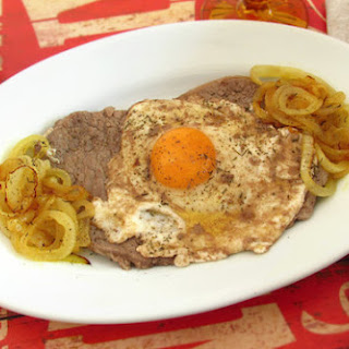 Fried Steaks With Onion And Fried Eggs