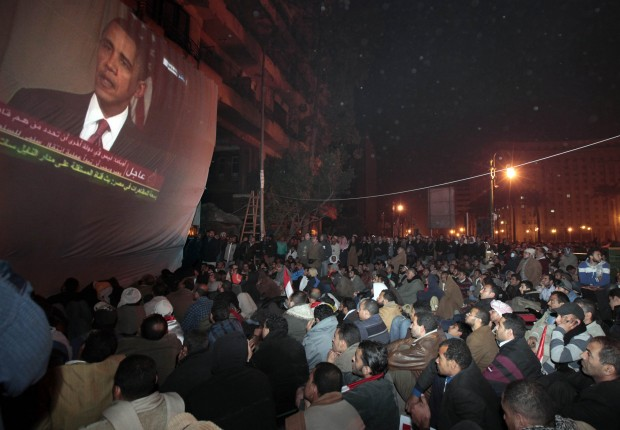 FILE - In this Wednesday, Feb. 2, 2011 file photo, anti-government protesters gathered in Tahrir (Liberation) Square, watch a screen showing U.S. President Barack Obama live on a TV broadcast from Washington, speaking about the situation in Egypt. U.S. officials say the Obama administration delivered pointed warnings Tuesday, July 2, 2013 to three main players in the latest crisis to grip Egypt as hundreds of thousands of protesters flooded Tahrir Square in Cairo to demand President Mohammed Morsi's ouster over his hard-line Islamist policies. The powerful Egyptian military appeared poised to overthrow him. The administration stopped short of demanding that Morsi take specific steps, the officials said, and instead offered strong suggestions that are backed by billions of dollars in U.S. aid to ease the tensions. (AP Photo/Lefteris Pitarakis)