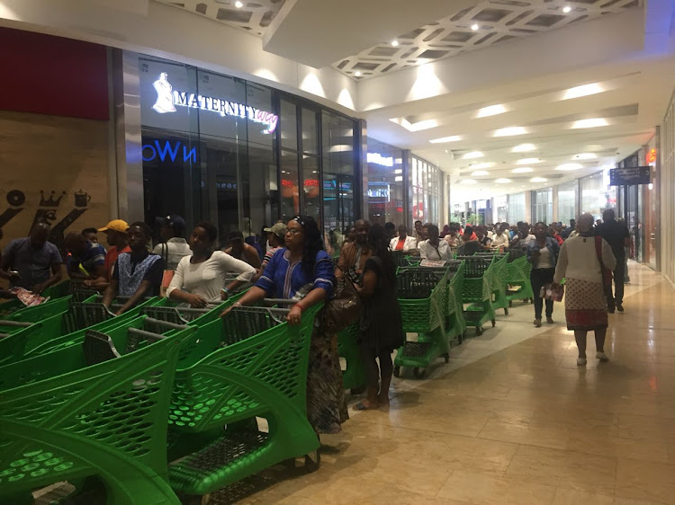 Customers queue at shopping shopping centre for Black Friday deals.
