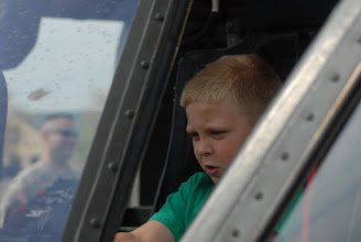 Photo: A child pretends to fly a UH-60 Blackhawk helicopter.