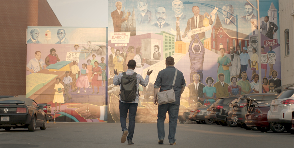 Founders, Justin and Bernard, are walking in front of a mural.
