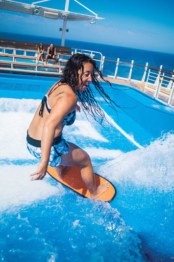 An instructor shows some rad moves on the FlowRider surf simulator on Harmony of the Seas.