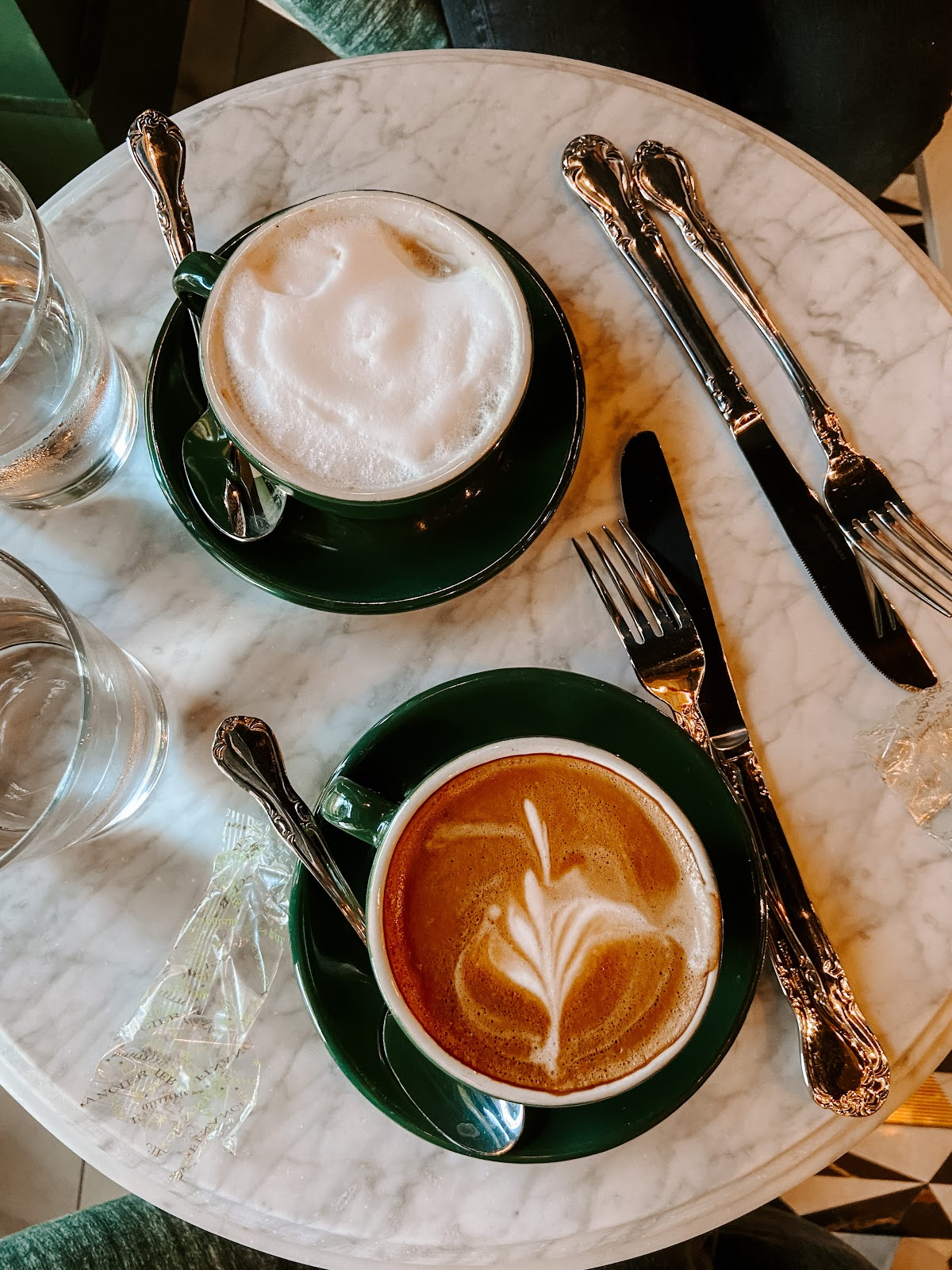 two cups of latte coffes on a circular marble table