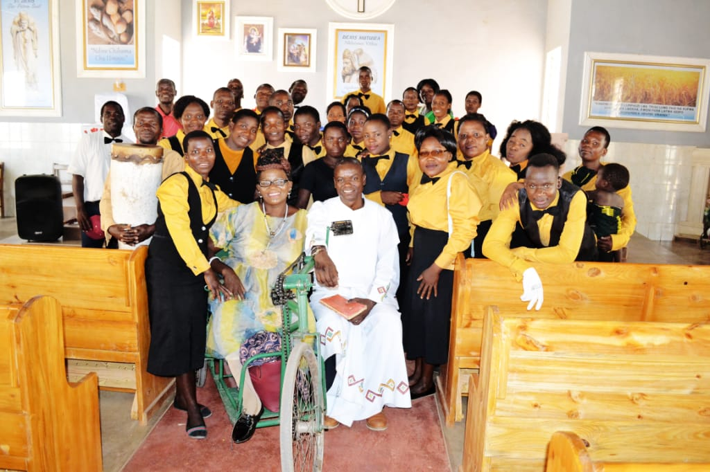 Image of the community with lady Mayimayi in her wheelchair with the choir and the parish priest seated to her left. Everybody smiling.