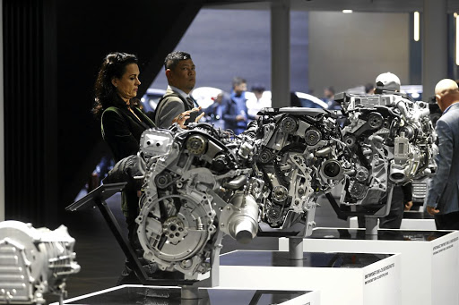 Valuation down: People look at BMW engines displayed at the Frankfurt Motor Show in this file photograph. The payoff of developing electric cars is uncertain, as high battery prices will squeeze returns for years. Picture: REUTERS