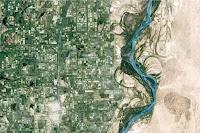Vue aérienne d'une rivière séparant une ville sur la gauche et un désert sur la droite