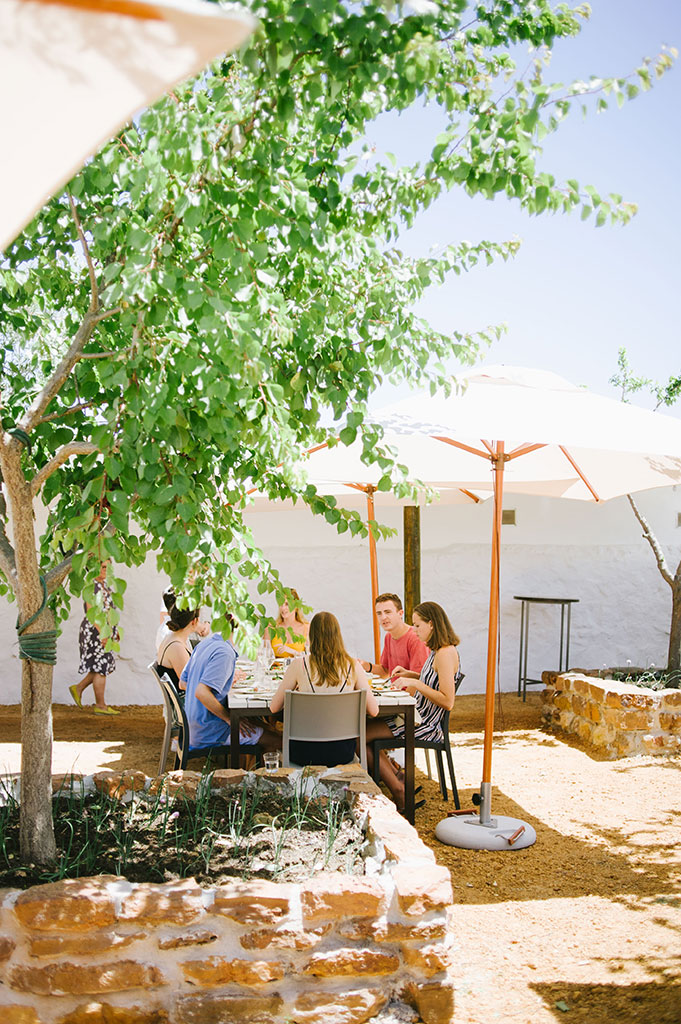 Cream tables in a shaded, stone courtyard – The Kraal has a stark Mediterranean feel.