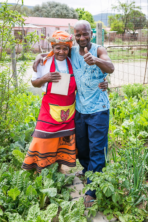 Bedford Township Garden Day competition winner Irene Nqobe celebrates with her son, Sgqibo Nqobe, in her garden