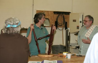 Photo: He described the method he uses to layout and drill the holes in the back of the seat to accept the leg tenons, showing the homemade jig that he uses on the drill press which gives the correct angle for the holes.  With emphasis on beauty of the wood, he prefers not drilling through the seat and showing the leg.