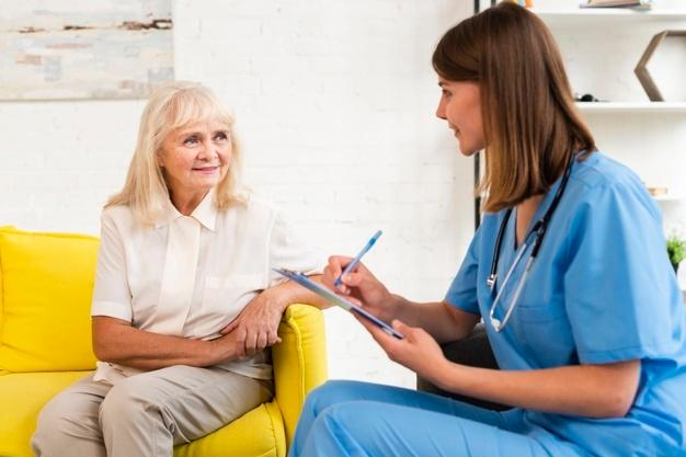 Medium shot old woman and caregiver talking