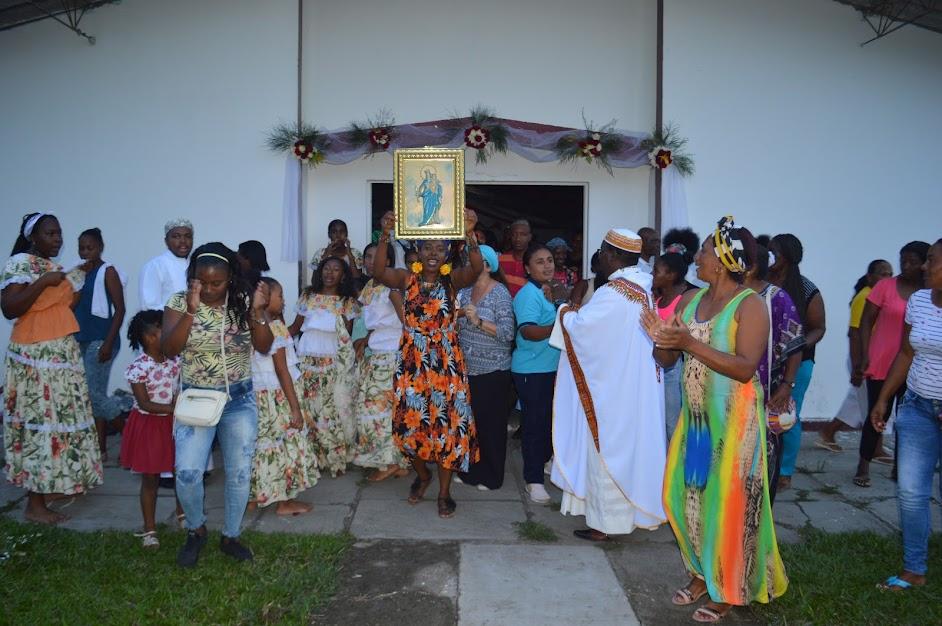 Una lideresa local levanta el cuadro de la Virgen a la entrada del templo de Santa Ana, en Miranda, Cauca. La rodean parroquianas, jóvenes del grupo de danza y agentes de la Pastoral Afro de Cali.