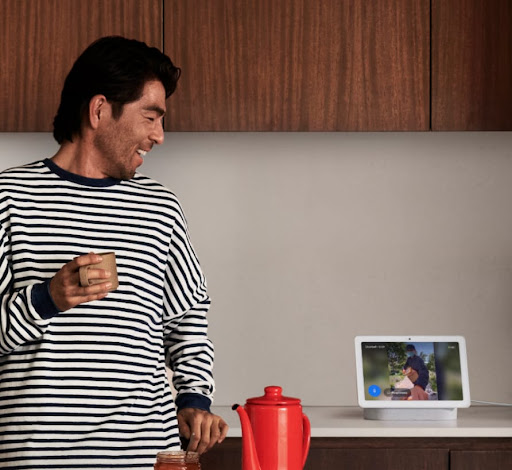 A man looks at Nest Hub in the kitchen.