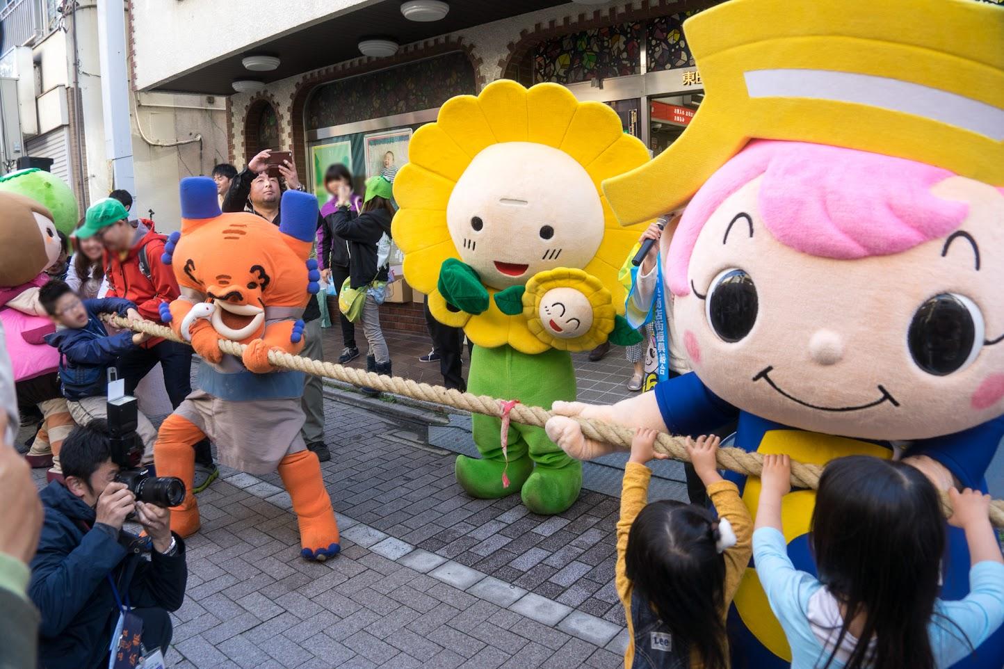 商店街の対抗綱引き合戦でひまわり咲ちゃん審判を勤める
