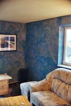 Photo: Wischtechnik extra grob. Durch die Art, Menge und Farbigkeit. Sowie Kontrast zum Untergrund lässt sich die Wirkung von Farbe stark beeinflussen. Durch den hellgrauen Untergrund und den Intensiven Kontrast wirkt die Oberfläche lebhaft aber auch Unruhig. Durch die hohe Transparenz der Blauen Lasur bleibt der Raum aber hell und freundlich.