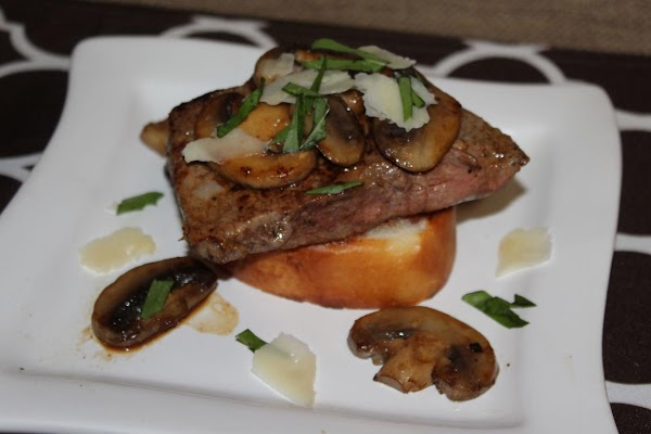 To serve, place steak on bread; top each serving with a mushroom and sprinkle...