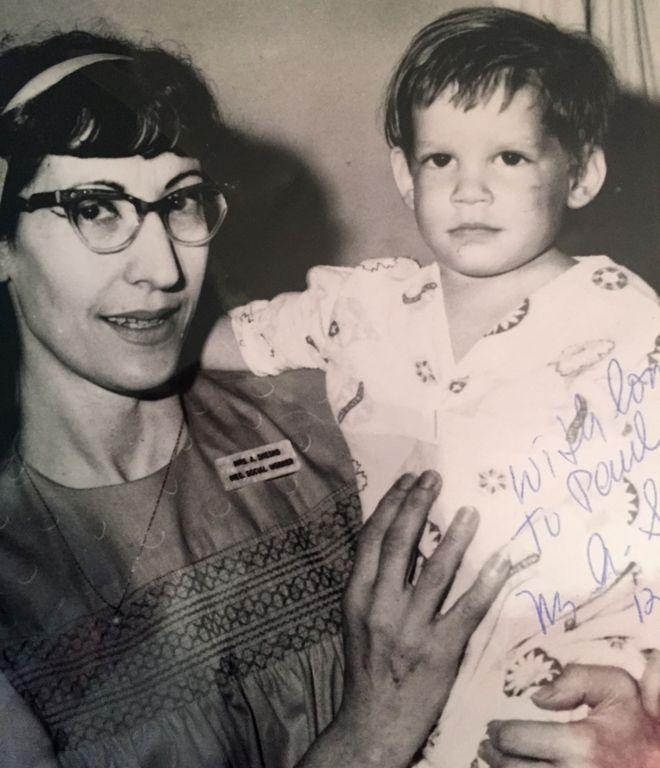 Сотрудница социальных служб держит на руках найденного мальчика с синяком на лице