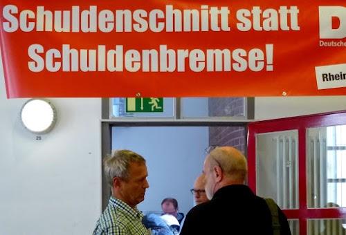 Transparent mit Losung: «Schuldenschnitt statt Schuldenbremse!» Außerordentliche Bezirksdelegiertenkonferenz Rheinland-Westfalen, 27. Oktober 2013.