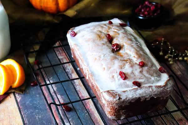 A Loaf Of Pumpkin Cranberry Bread With Orange Glaze.