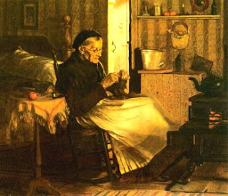 Photo: Granny knitting, warming herself in front of her old fashioned step stove, tea kettle simmering. Behind her you can see this is also her bedroom. When she was a young woman, rooms served several functions.
