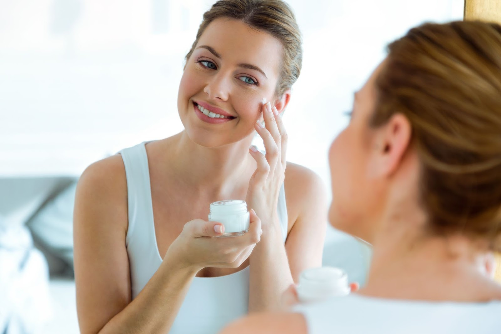 A woman applying a skincare product with active ingredients on her skin