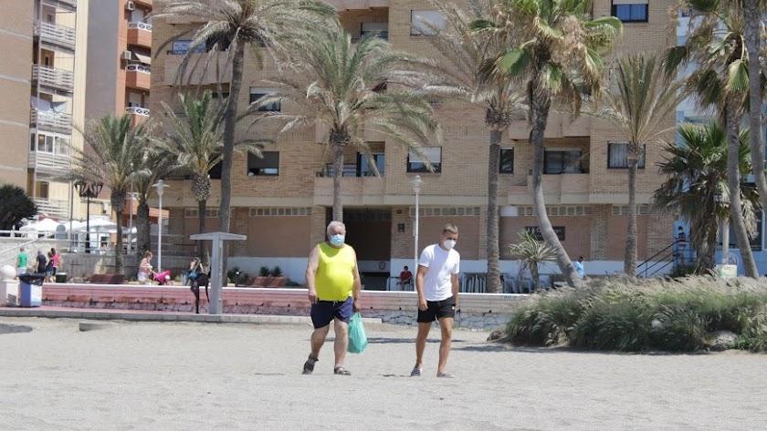 Almerienses con la mascarilla puesta para ir a la playa.