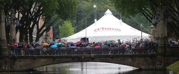 Die Brücke voller Menschen mit Regenschirmen.