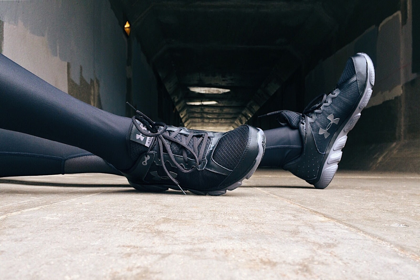 This is a photo of black athletic shoes on a pair of feet wearing black athletic leggings.