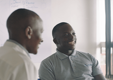 Founder, Gerald Otim, smiles at a table with colleagues.