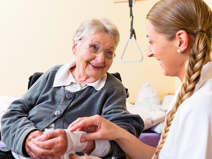 Ärztin im Gespräch mit einer älteren Patientin - langsam heilende Wunden gehören bei Diabetes in ärztliche Behandlung.