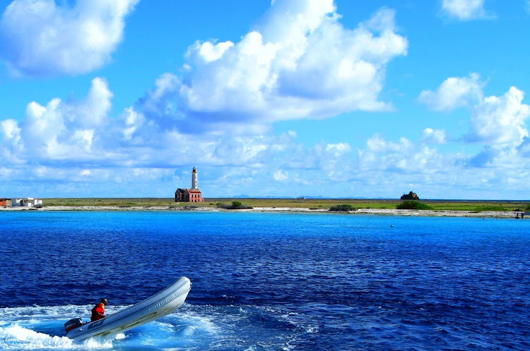 A speedboat explores the coast of Klein Curacao, with the lighthouse in the background.
