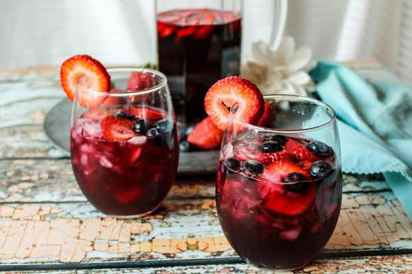 Two Glasses And A Pitcher Of Blueberry Hibiscus Sangria.