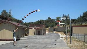 A student playing basketball with a hoop on a post.