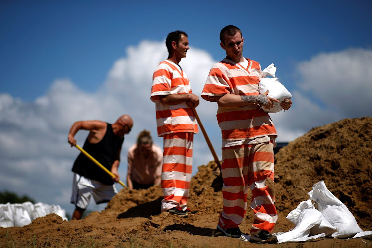 Inmates fill bags with sand as Tropical Storm Gordon approaches Bay St Louis, Mississippi.