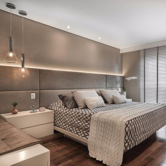 Quarto com cama de casal com cabeceira de estofado larga cinza, piso de madeira e luminária pendente.