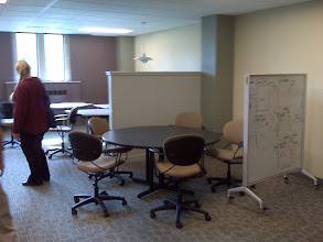 Photo: more moveable whiteboards around portable table and chairs, inviting movement/rearrangement.