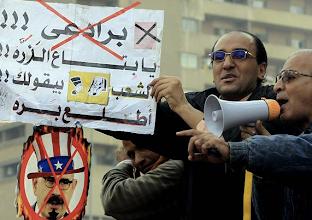Photo: Un manifestante egipcio muestra un cartel con el mensaje en árabe «El Baradei, tu equipo de científicos nucleares quiere que te marches». Fotografía: KHALED ELFIQI | EFE
