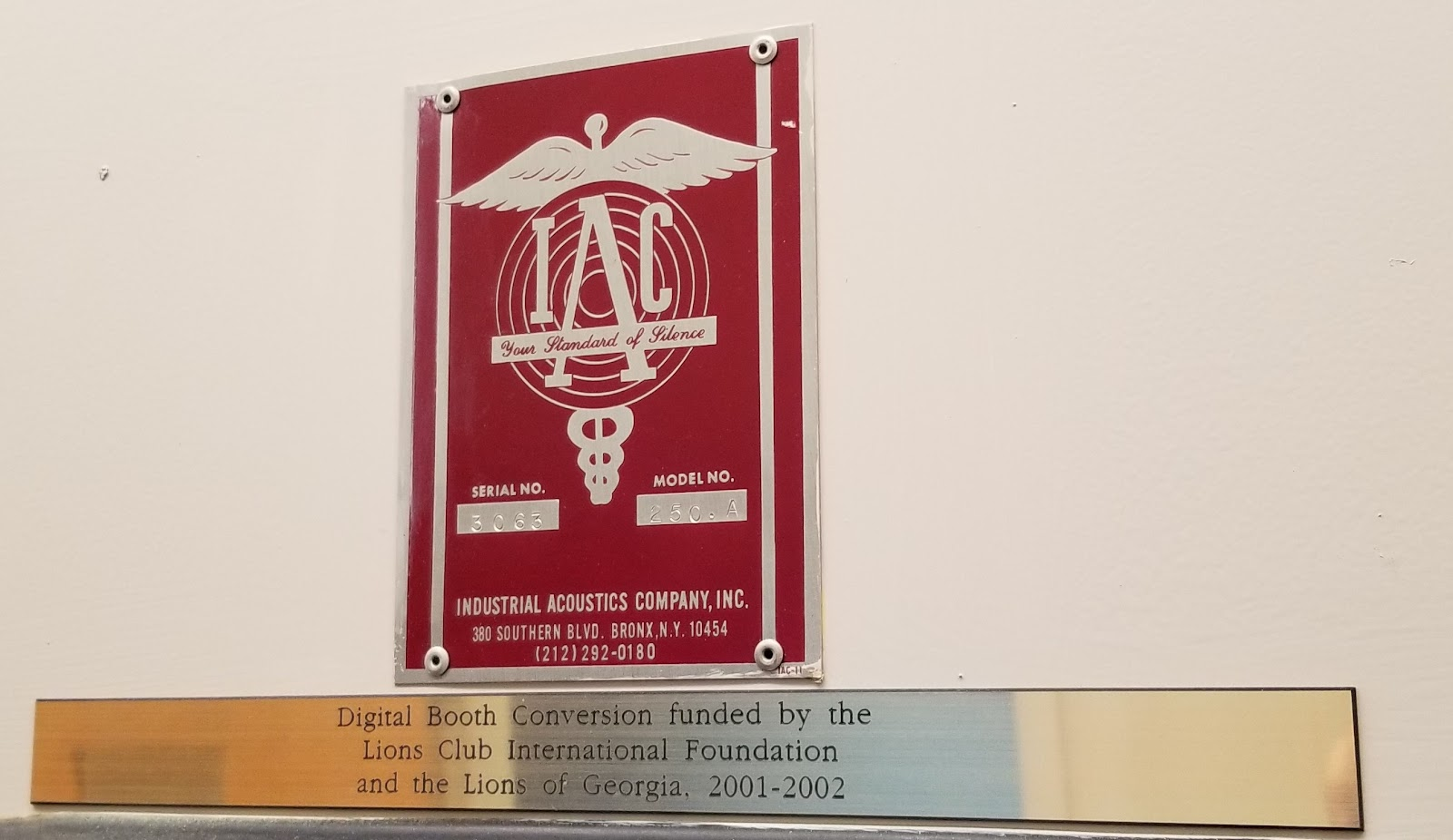 Two plaques on a recording booth door:  (1) manufacturer's logo and contact information; (2) Digital Booth Converrsion funded by the Lions Club International Foundation and the Lions of Georgia, 2001-2002
