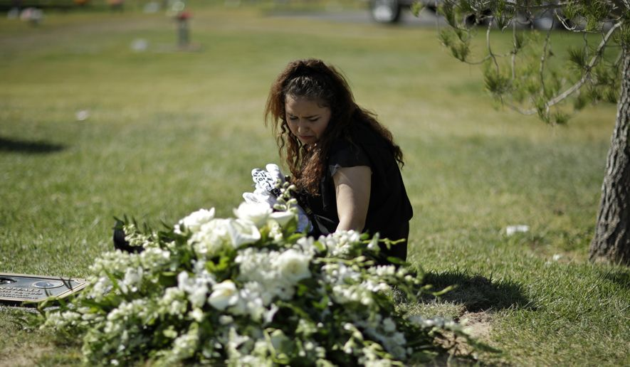 Chantel Sosa cries at the graveside during a funeral for her brother Erick Silva, Thursday, Oct. 12, 2017, in Las Vegas. Silva was working as a security guard when he was killed during a mass shooting Oct. 1, in Las Vegas. (AP Photo/John Locher)