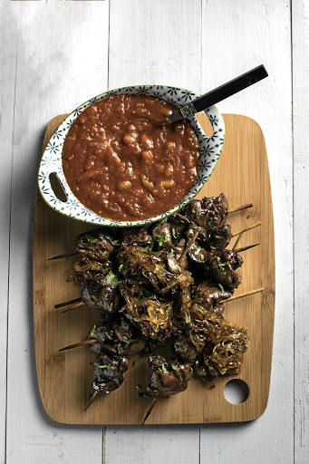 Chicken liver skewers with caramelised onions, pictured with a bowl of chakalaka.