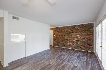 Living room with wood-inspired flooring and brick accent wall