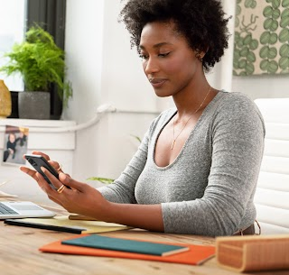 A woman seated at a desk, using an Android phone.