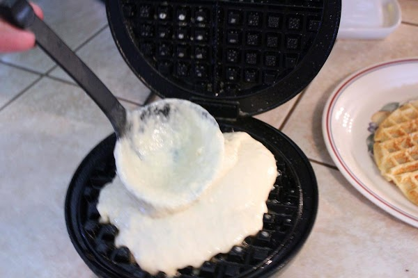 Adding batter to hot waffle iron.