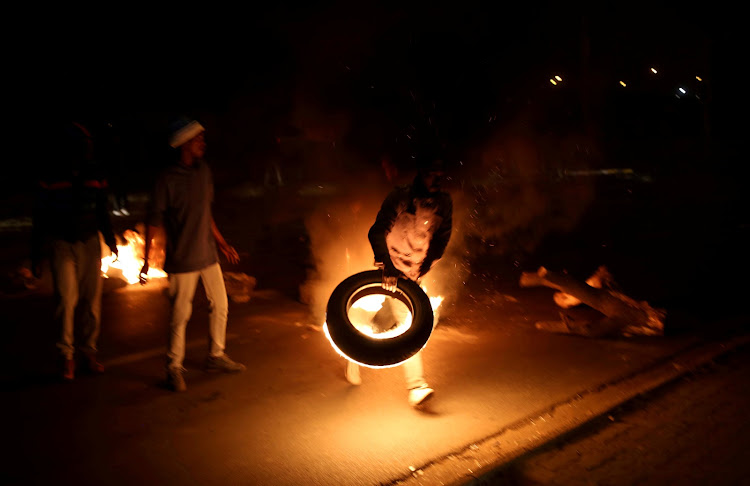 A man blocks a road with a burning tyre while protesting against electricity cuts in Klipspruit Soweto.
