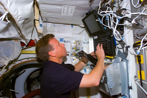 Lindsey enters data into laptop in Spacehab
