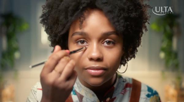 Miniaturansicht einer Schwarzen Frau, die Gesichts-Make-up aufträgt