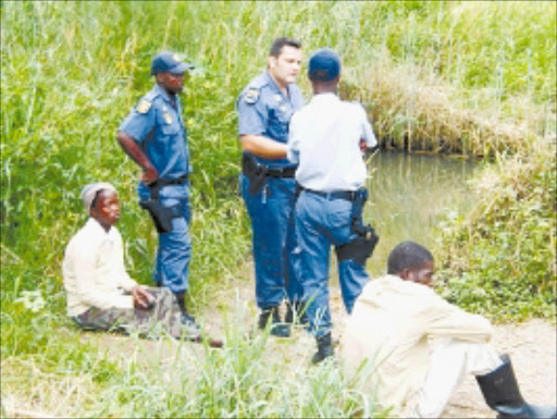 Searching: Police consider their next move at the river where Nkonzo Nzuza was last seen. The boy's mother, Nokuthula Zulu, and uncle Sifiso Biyela are devastated. Pic. Unknown.