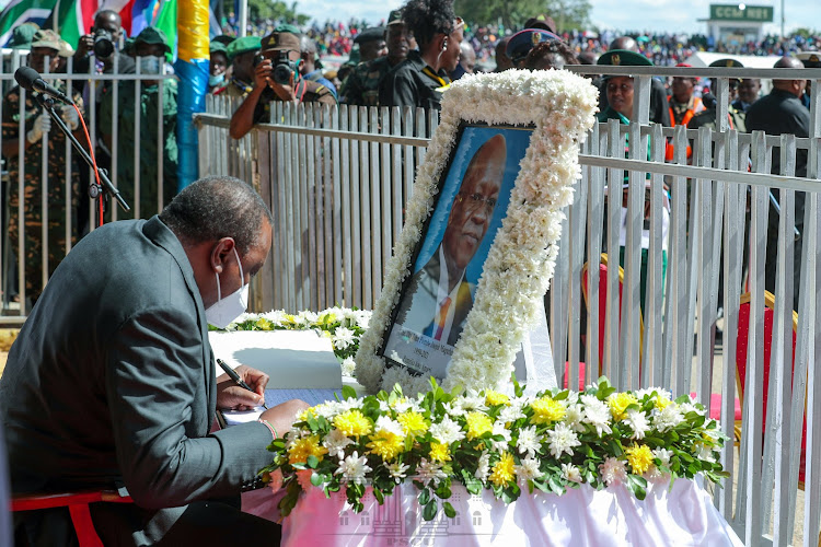 President Uhuru Kenyatta signs the condolence book at Jamhuri Stadium in Dodoma, Tanzania for the State Funeral of former President Dr John Pombe Joseph Magufuli on March 22, 2021.