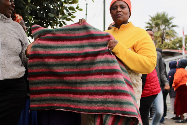Nozuko Mendela holds up the blanket she received from disaster relief
